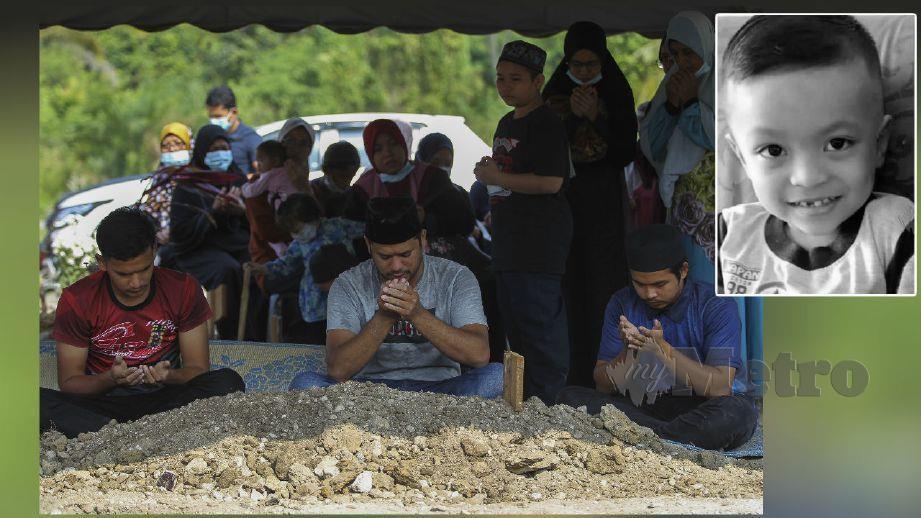 MOHD Bukhari Zainal (tengah) membacakan doa buat anaknya Allahyarham Muhammad Fawwaz Adli di Tanah Perkuburan Islam Senawang. FOTO Azrul Edham Mohd Aminuddin