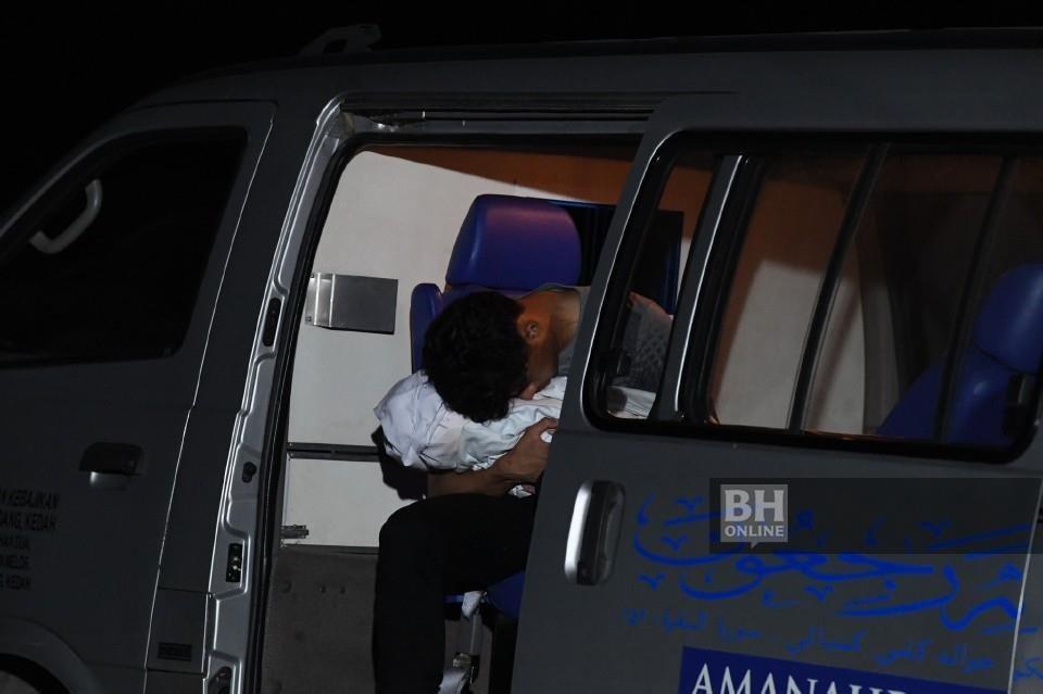 Muhammad Syafiq memangku dan memeluk erat jenazah anaknya Muhammad Aisy Saqeef Muhammad Syafiq untuk dikebumikan di Tanah Perkuburan Islam Bukit Murai Kampung Padang Pusing, Pendang. - Foto BERNAMA
