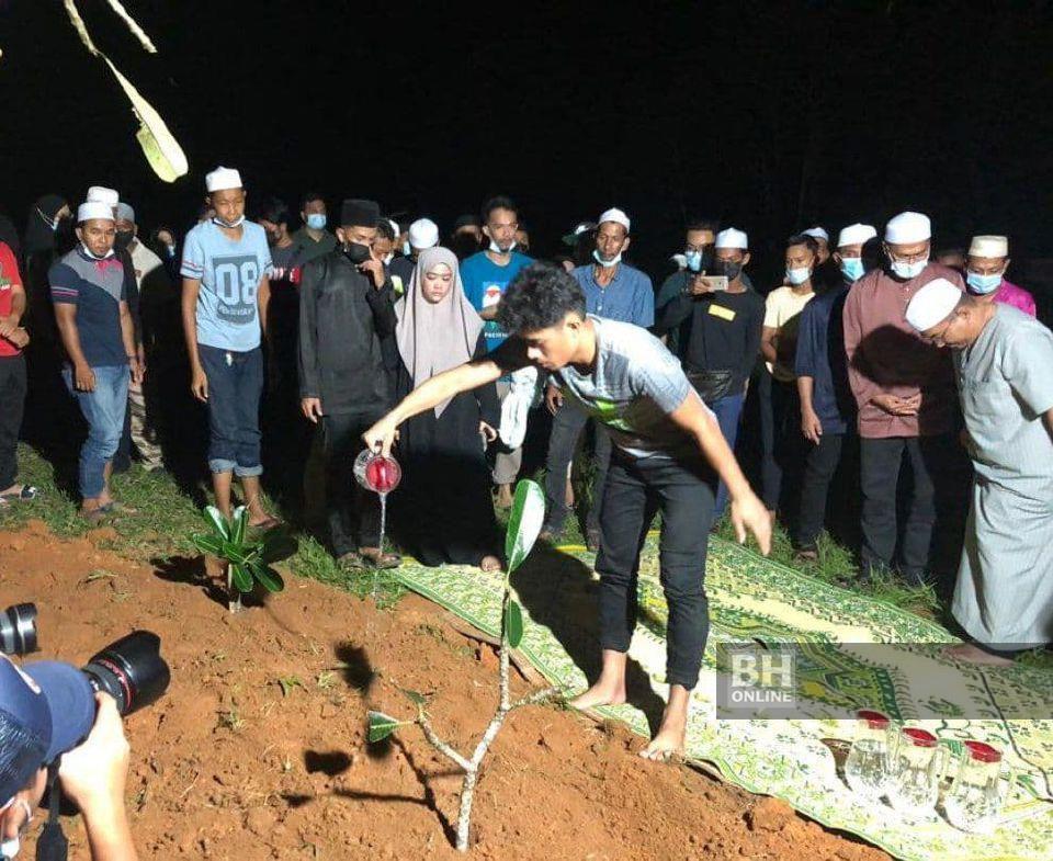 Muhammad Syafiq menyiram air mawar di pusara ibu mentuanya dan anak lelakinya di Padang Pusing, Pendang. - NSTP/Zuliaty Zulkiffli