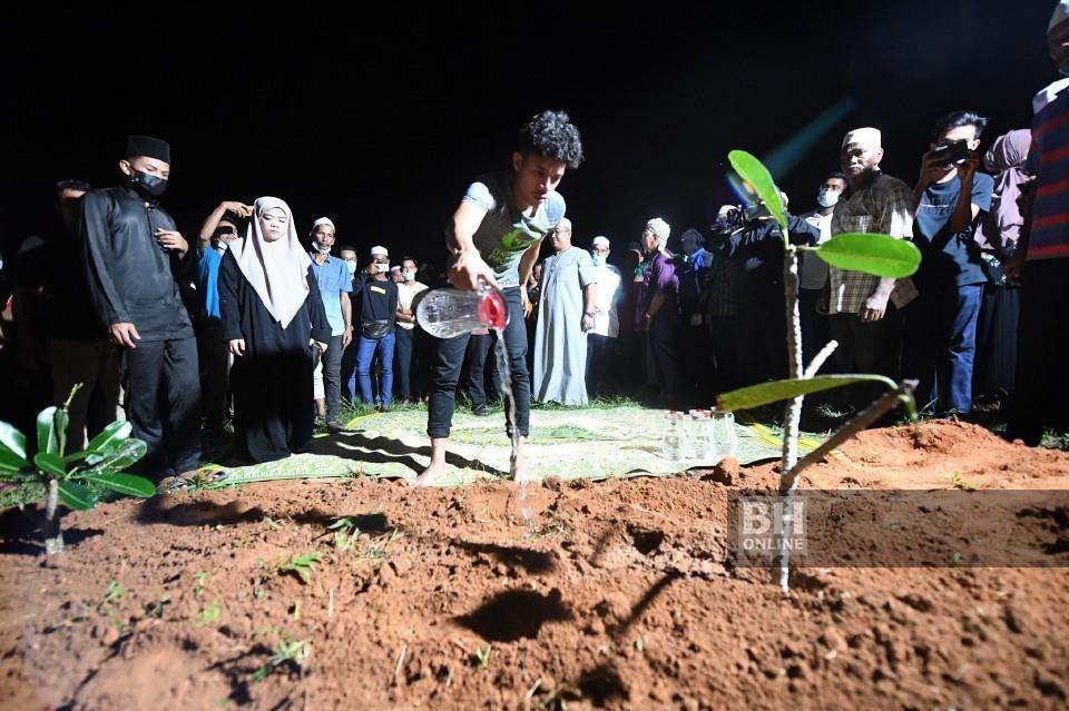 Muhammad Syafiq menyiram air mawar ke pusara anaknya Muhammad Aisy Saqeef yang dikebumikan dalam satu liang lahad bersama neneknya Zainab Wahab, di Tanah Perkuburan Islam Bukit Murai Kampung Padang Pusing di Pendang. - Foto BERNAMA