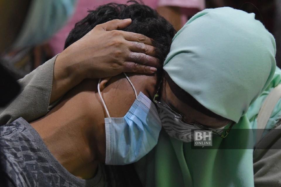 Muhammad Syafiq sebak di sisi jenazah anaknya yang berusia 22 hari dan jenazah ibu mentuanya Zainab Wahab, yang baru tiba di Kampung Padang Pusing dari Unit Forensik Hospital Sungai Bakap. - Foto BERNAMA